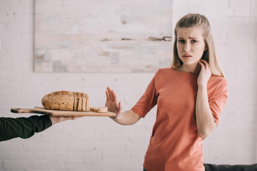 Dziewczyna z alergią pokarmową odsuwa od siebie deskę, na której leży pokrojony chleb.