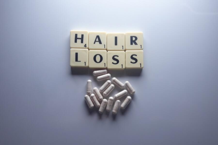 Suplement diety w kapsułkach i płytki do gry Scrabble ułożone w słowa