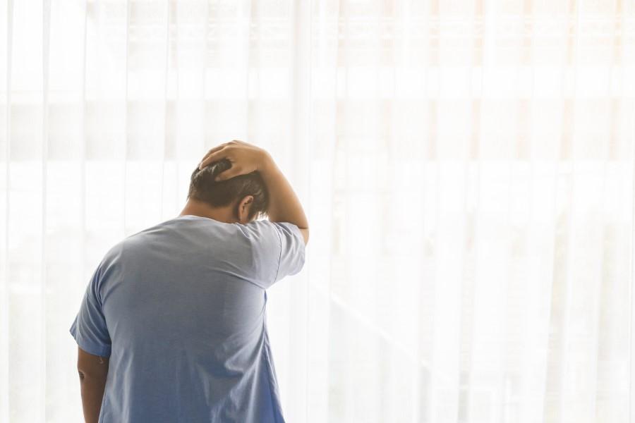 Mężczyzna stoi przy oknie, trzyma się za tył głowy.