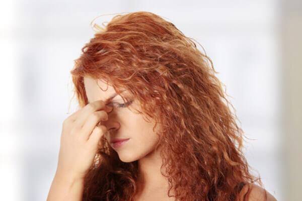 kobieta trzymająca sie za nos z powodu bólu zatok