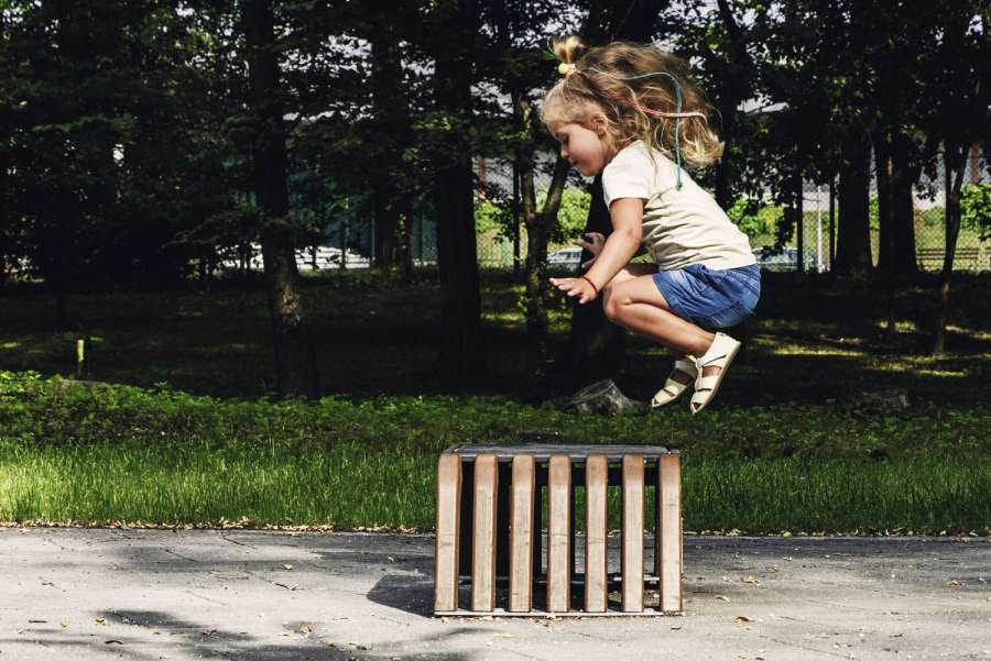 Dziewczynka w barefootowych butach wskakuje na skrzynię - Sklep z butami dla malucha Bosa Stópka