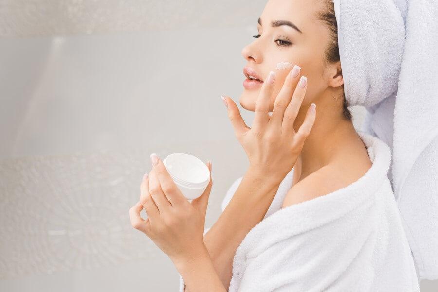Kobieta w szlafroku i ręczniku na głowie. Smaruje twarz kremem.