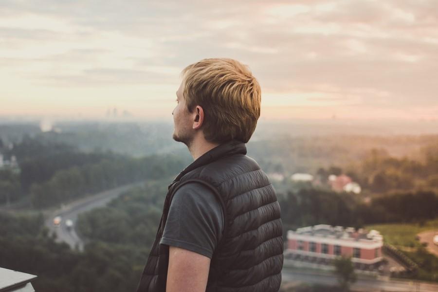 Mężczyzna w kamizelce patrzy na panoramę miasta.