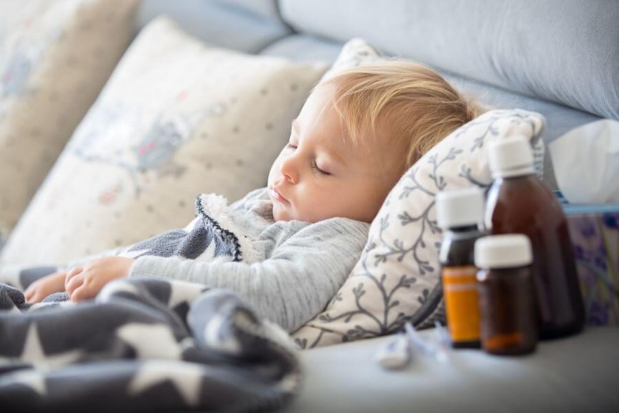 Przeziębiony chłopczyk leży w łóżku, obok stoją leki, chusteczki higieniczne i termometr.