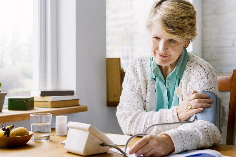 Starsza kobieta mierzy ciśnienie krwi ciśnieniomierzem naramiennym.