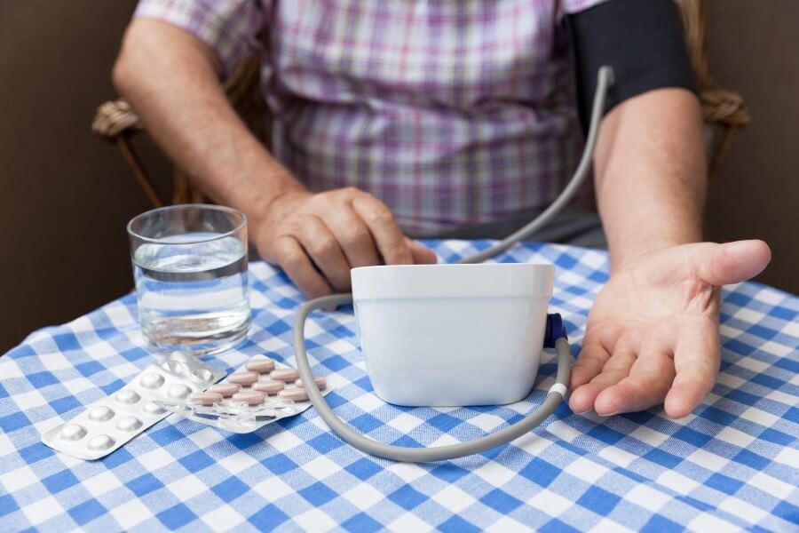 Mężczyzna wykonuje pomiar ciśnienia ciśnieniomierzem. Na stole leżą listy leków i szklanka wody.