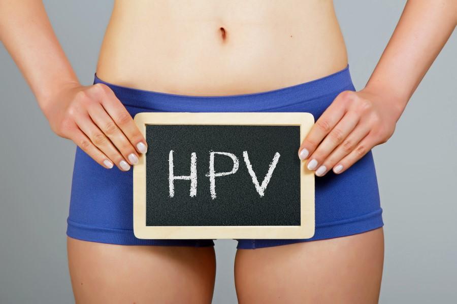 Kobieta w bieliźnie, na wysokości bioder trzyma niewielką tablicę kredową z napisem HPV.
