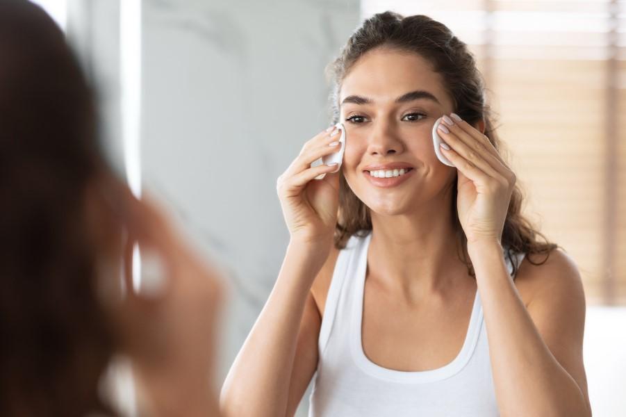 Kobieta w łazience podczas pielęgnacji skóry twarzy.
