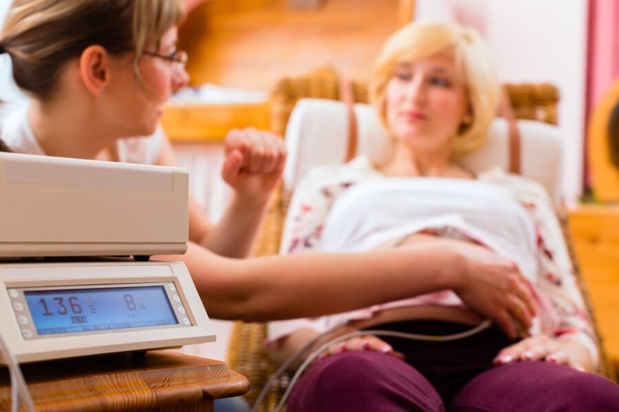 Położna przeprowadza u kobiety w ciąży badanie przy pomocy detektora tętna płodu.