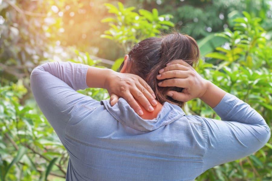 Kobieta odczuwa ból karku związany z fibromialgią.