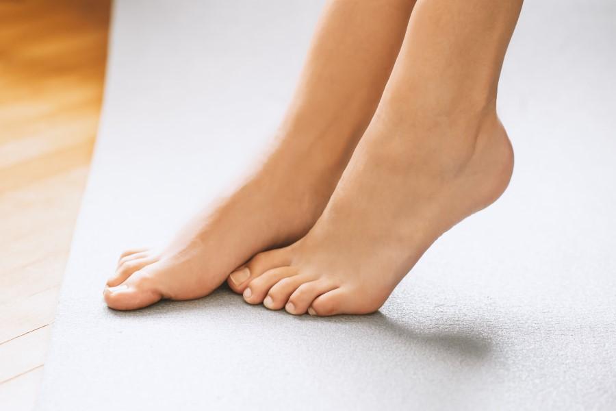 Damskie, zadbane stopy na szarej macie do ćwiczeń.