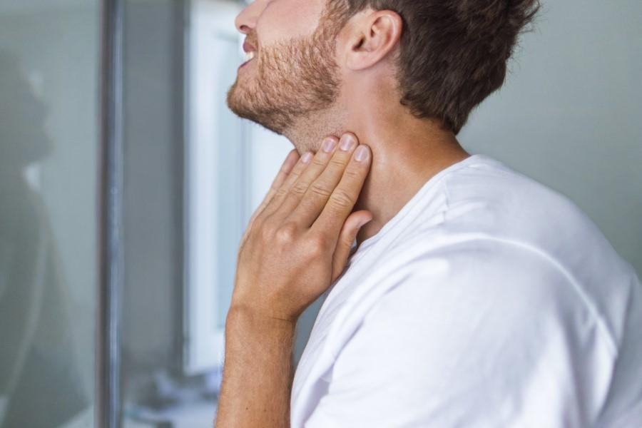 Mężczyzna trzyma się za szyję, choruje na chorobę Hashimoto.