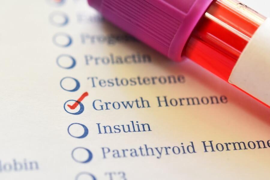 Fiolka z próbką krwi leżąca na kartce z wylistowanymi hormonami. Wyróżniony hormon wzrostu.