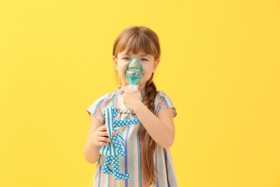 Dziewczynka korzysta z inhalatora, w drugiej ręce trzyma ulubioną zabawkę.