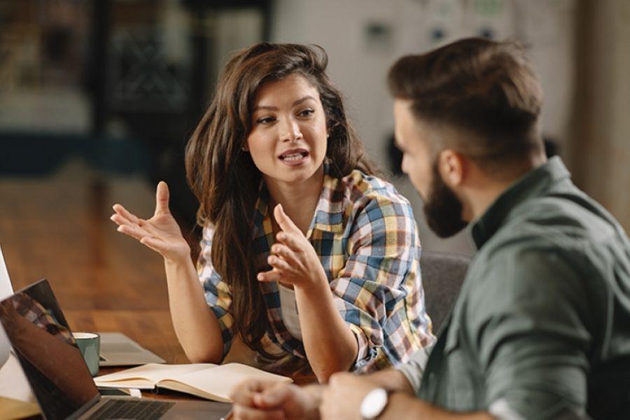 Kobieta i mężczyzna, siedzą przy laptopach i rozmawiają gestykulując.