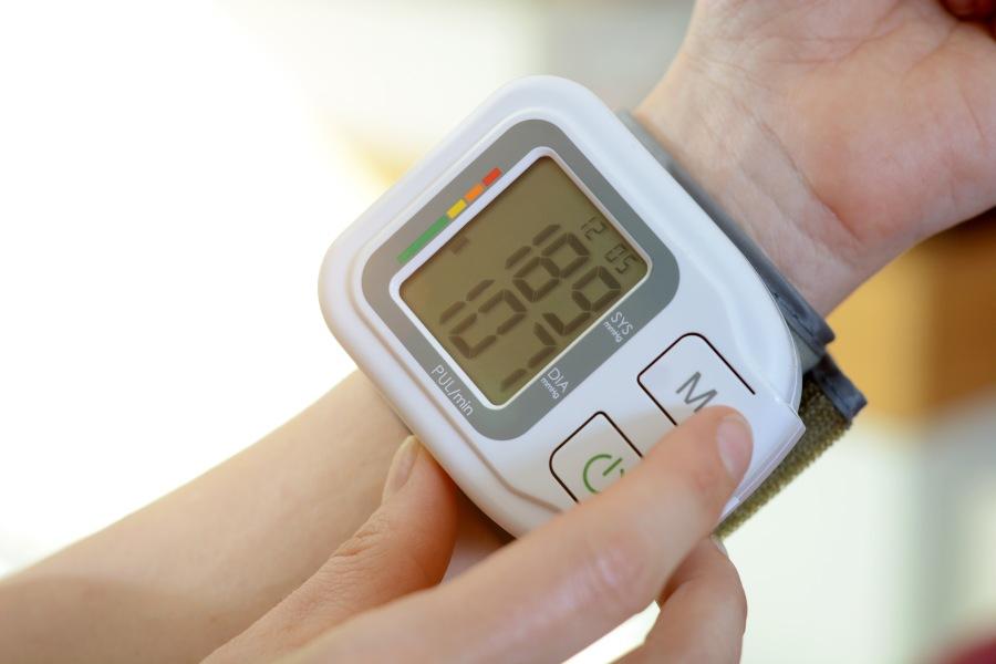 Założony na rękę ciśnieniomierz nadgarstkowy, pokazuje wysokie wartości ciśnienia tętniczego.