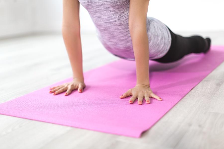 Kobieta w stroju sportowym ćwiczy jogę na różowej macie do ćwiczeń