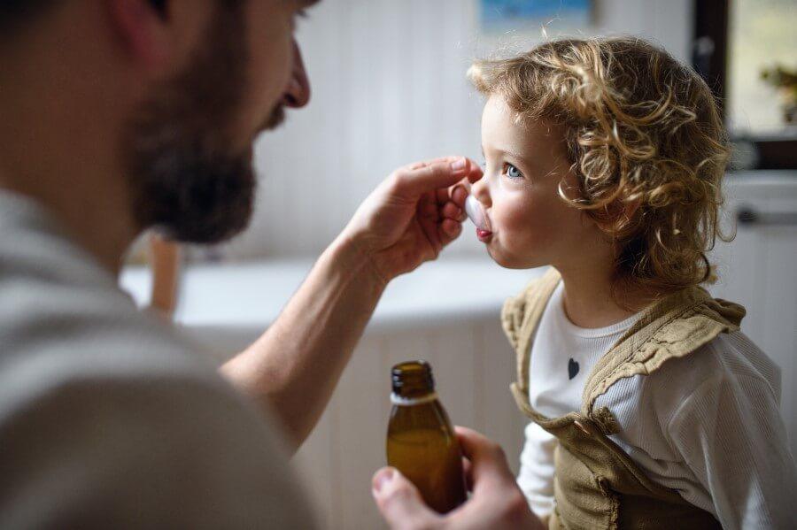 Ojciec podaje dziecku syrop na kaszel.