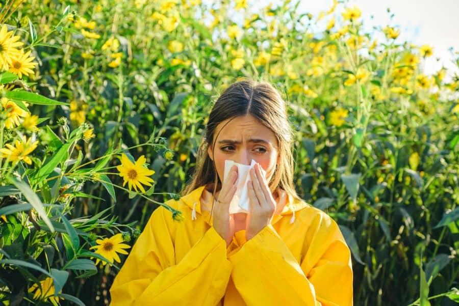 Kobieta w żółtej kurtce, pośród kwiatów. Wydmuchuje nos, bo cierpi na katar alergiczny.