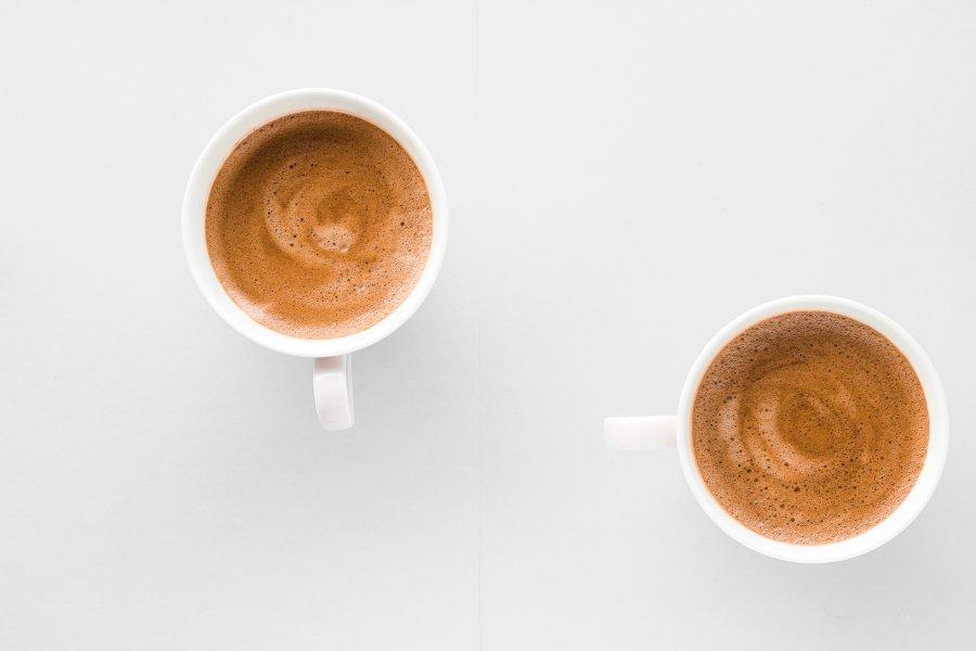 Dwa białe kubki z kawą bezkofeinową leżą na blacie kuchennym