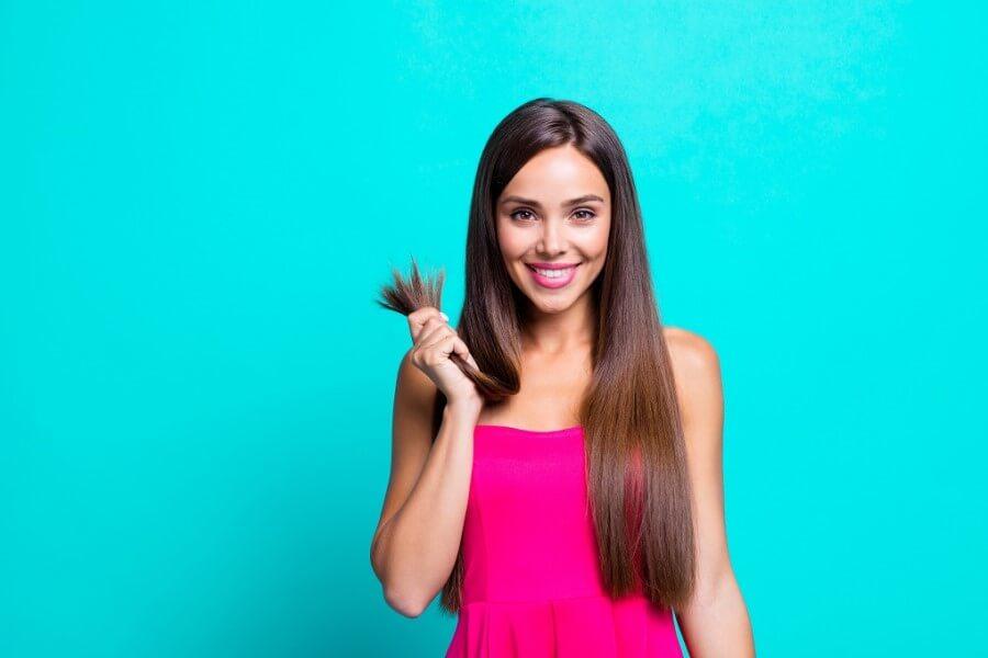 Uśmiechnięta kobieta w różowej sukience. Trzyma w dłoni pukiel swoich zadbanych włosów.