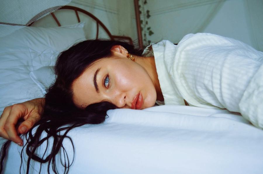 Młoda kobieta leży na łóżku, wygląda na przemęczoną.