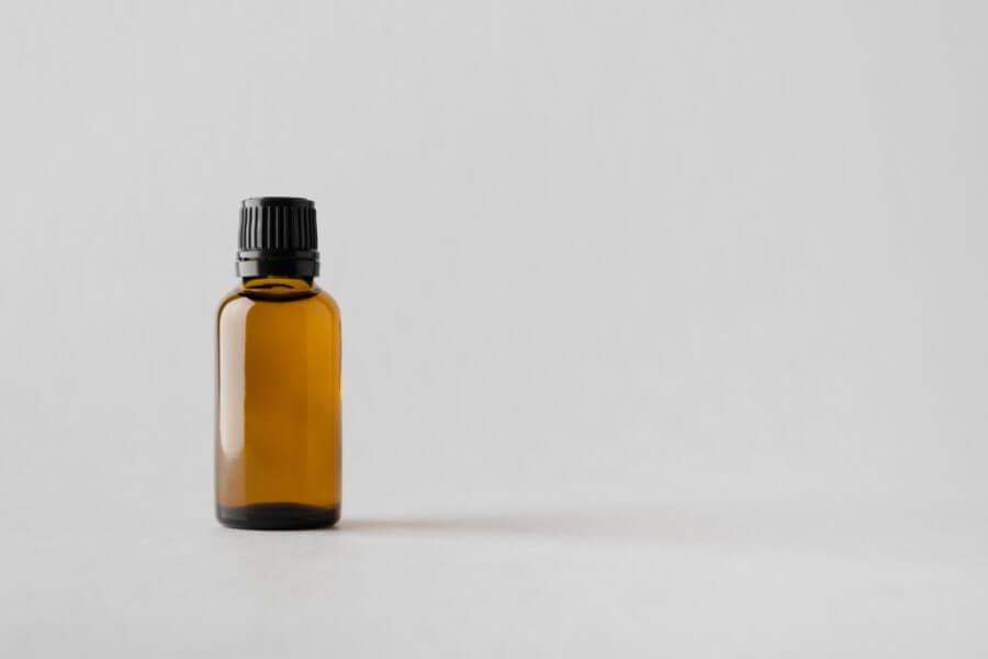 Szare tło. Buteleczka z brązowego szkła zawierająca produkt leczniczy w postaci kropli.