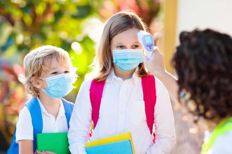 Mali uczniowie w maseczkach. Nauczycielka sprawdza dzieciom temperaturę termometrem bezdotykowym.