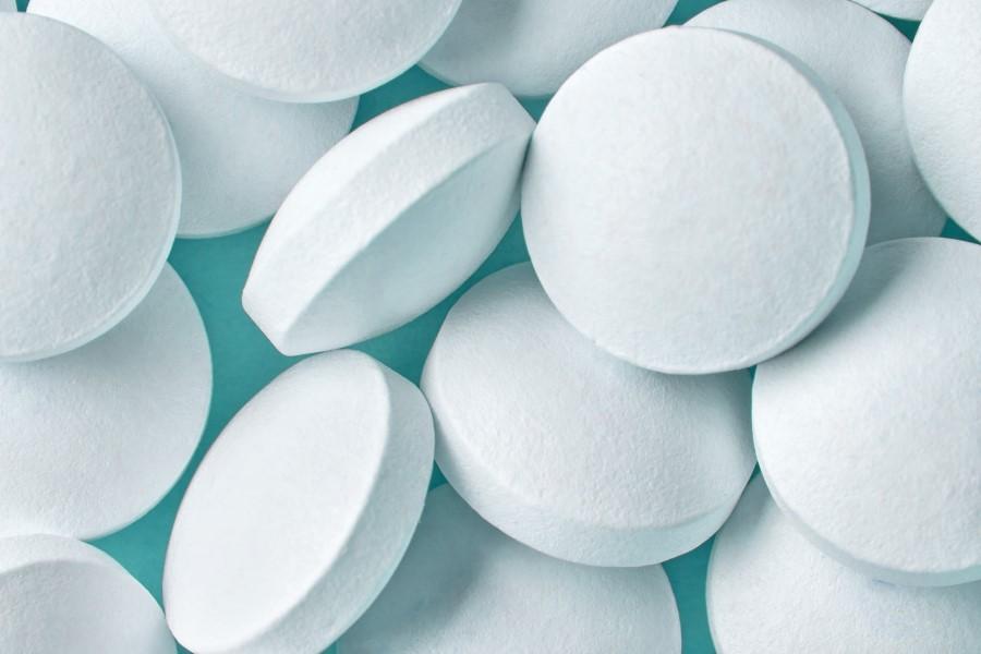 Białe tabletki na turkusowym tle.