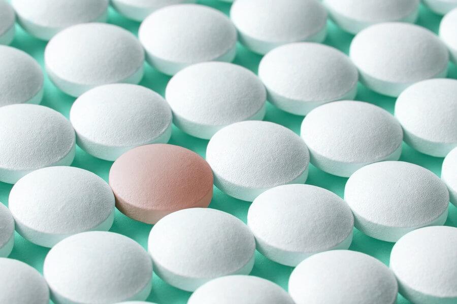 Białe tabletki na turkusowym tle. Pośród nich widoczna jedna, różowa tabletka.