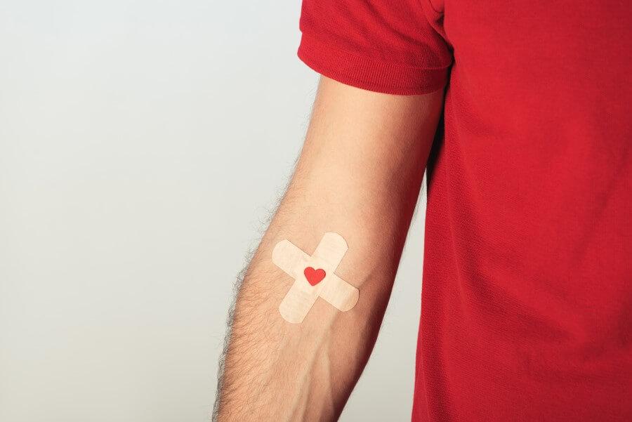 Mężczyzna w czerwonym t-shircie. Na zgięciu łokciowym na naklejony plaster po oddaniu krwi.