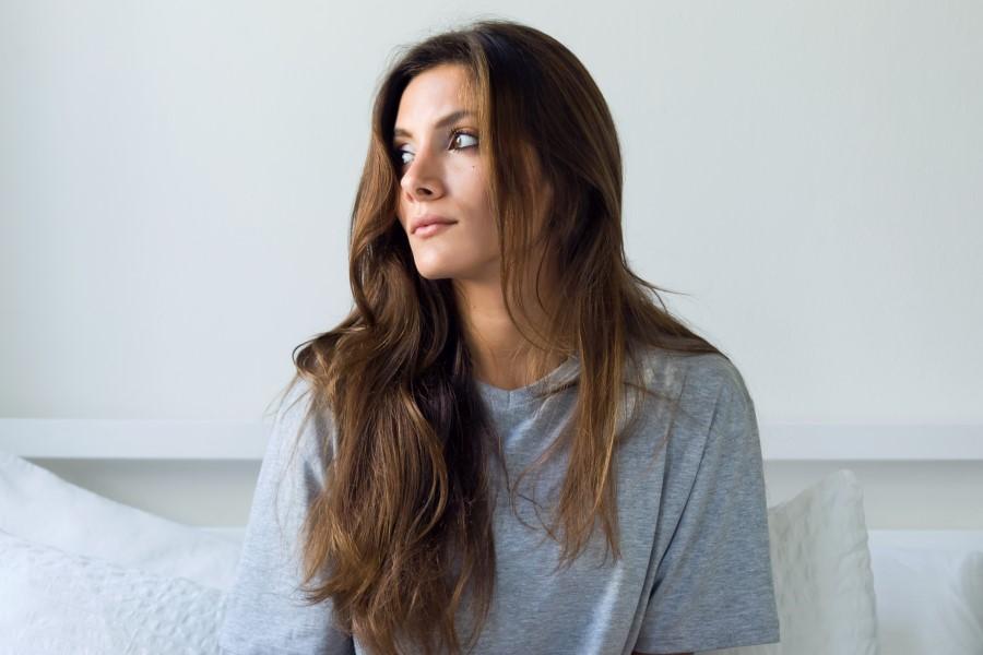 Długowłosa brunetka siedzi na kanapie, spogląda w stronę okna.