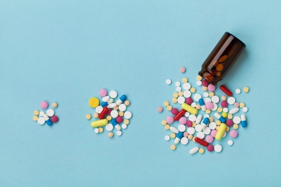 Niebieskie tło. Buteleczka z brązowego szkła, obok rozsypane kolorowe tabletki i kapsułki.