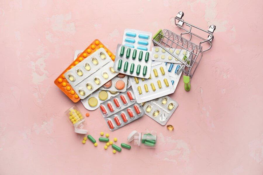 Przewrócony, zabawkowy wózek sklepowy, a w nim blistry różnych tabletek i kapsułek.