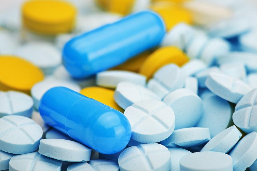 Wymieszane żółte i błękitne tabletki oraz niebieskie kapsułki.