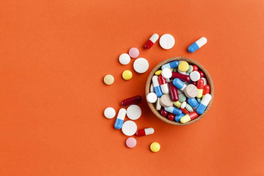 Kapsułki i tabletki na pomarańczowym tle.