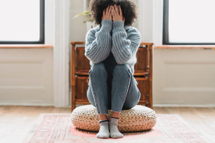 Kobieta siedzi na jutowej pufie, zasłania twarz dłońmi.