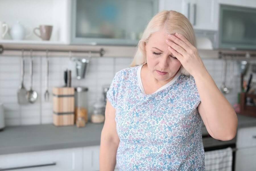 Kobieta w kuchni, trzyma się za głowę, jest obolała i przemęczona.
