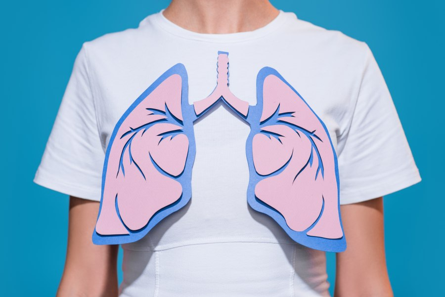 Kobieta w białej koszulce, do koszulki przymocowane płuca, wycięte z kolorowego papieru.
