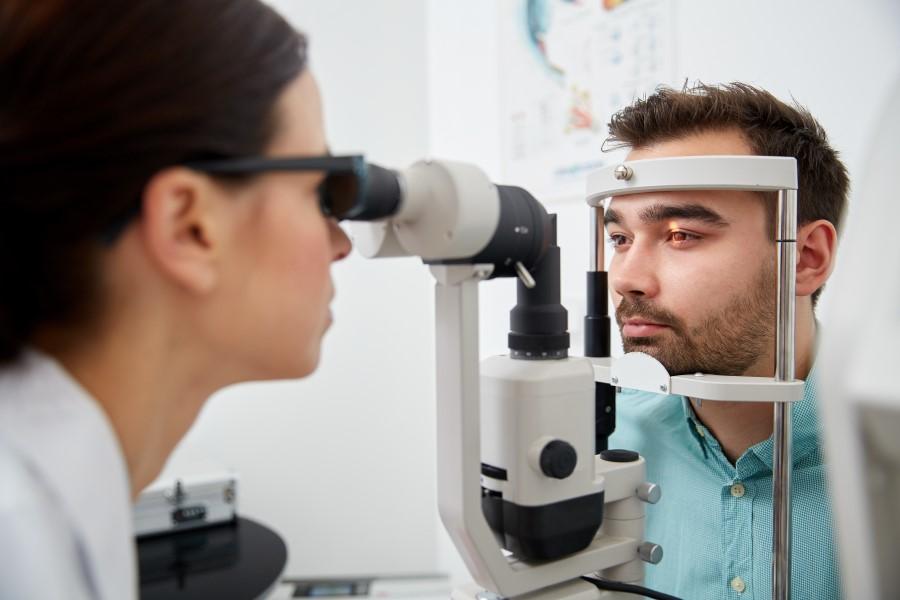 Mężczyzna bada się u okulisty w kierunku diagnostyki nadciśnienia w oku.