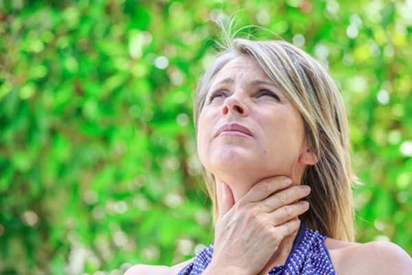 kobieta trzymacjąca sie za gardła - nadczynność tarczycy