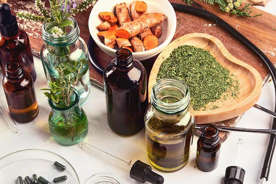 Świeże i suszone zioła oraz pipeta i butelki na drewnianym blacie.