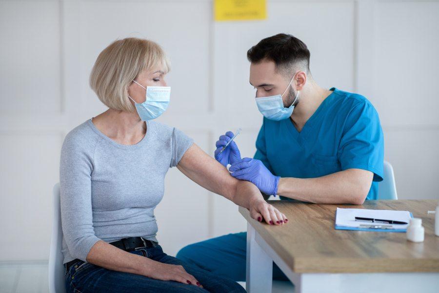 Kobieta zostaje zaszczepiona przeciwko COVID-19 przez pielęgniarza. Oboje są w maseczkach.