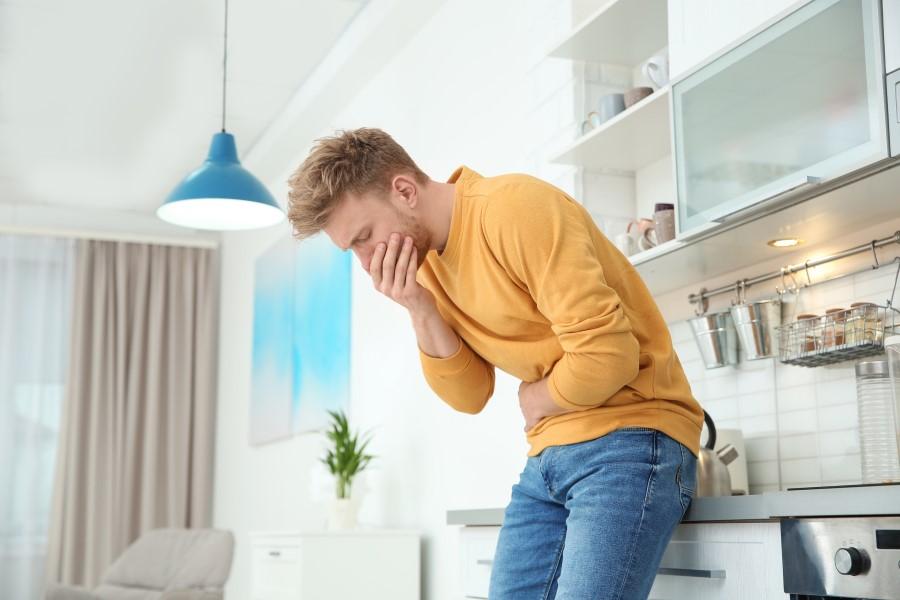 Mężczyzna stoi w kuchni. Trzyma się za brzuch i buzię, odbija mu się po jedzeniu.
