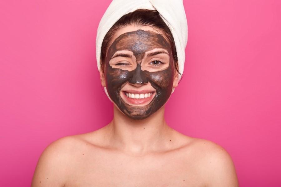 Kobieta z ręcznikiem na głowie i oczyszczającą maseczką na twarzy, uśmiecha się do obiektywu.