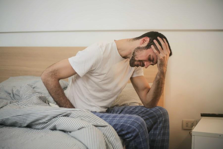 Mężczyzna w piżamie siedzi na brzegu łóżka, trzyma się za głowę, źle się czuje.