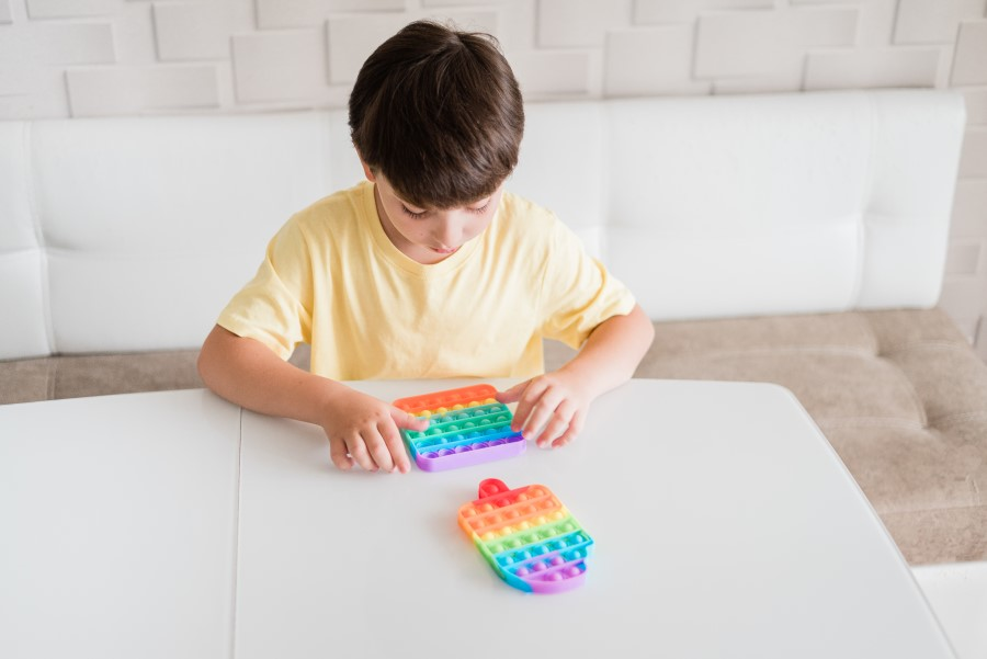Chłopiec siedzi przy stole, bawi się kolorową zabawką.