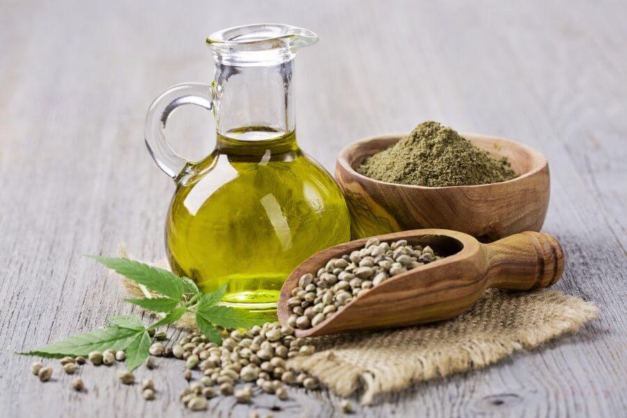 Butelka oleju konopnego oraz nasiona konopi (w całości i zmielone).