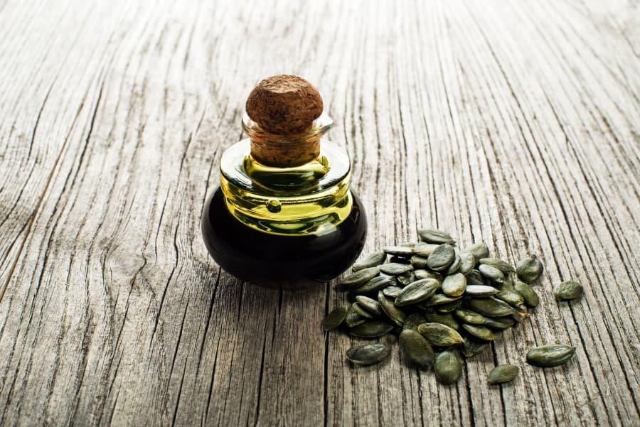 Butelka oleju z pestek dyni i pestki dyni na drewnianym blacie.