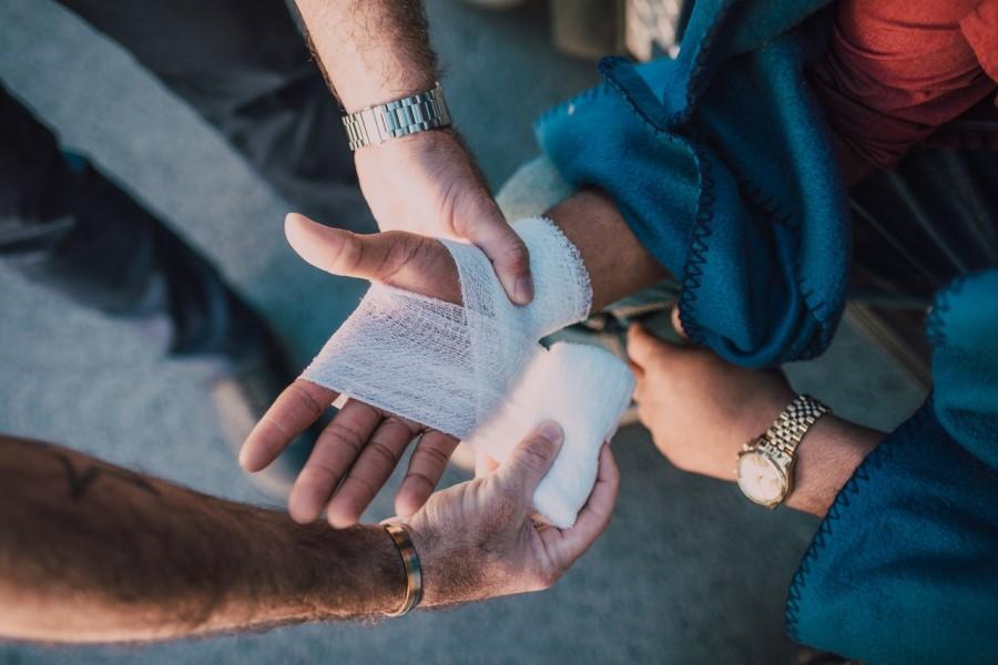 Mężczyzna opatruje dłoń kobiety, która uległa wypadkowi.